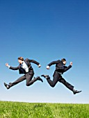 businessmen jumping in field