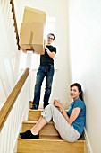 A couple on the stairs with boxes