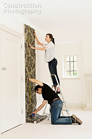 A couple putting up wallpaper