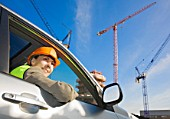 Woman in car at building site