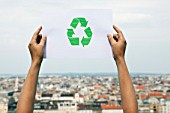 Arms holding paper green recycling sign