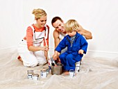 Couple and boy mixing paint in bucket