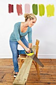 Woman sawing plank