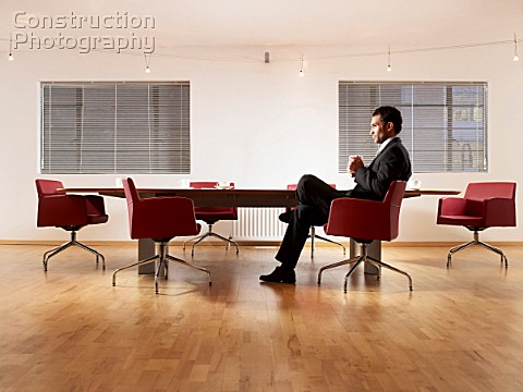 Man in suit sitting at boardroom table