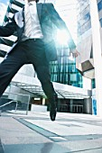Businessman Leaping on City Street