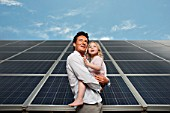 Man and daugther in front of solar panel