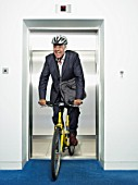 man riding a bicycle out of a lift