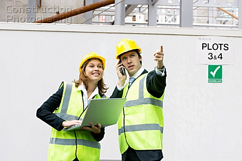Team of young professionals on a construction site wearing hard hat and using laptop computer and mo