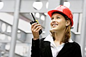 Young woman on a construction site wearing a hard hat and using a walkie talkie.