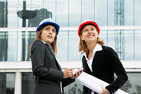 Young women on a construction site wearing a hard hat