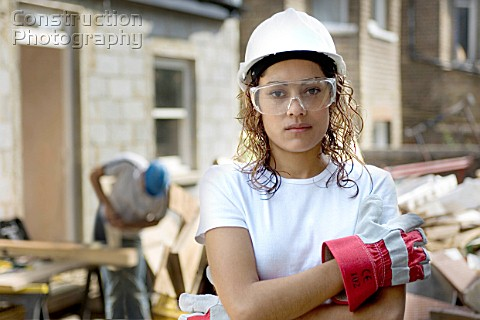 Young woman on a construction site wearing a hard hat