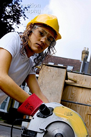 Young woman using a circular saw on a construction site with hard hat