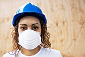 Young woman on a construction site with hard hat and mask.