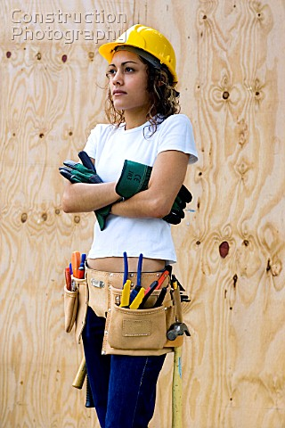 Young woman on a construction site with hard hat and Tool belt