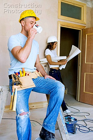 Male builder having a break and woman site manager reading plans