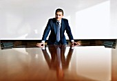 Businessman leaning on a boardroom table.