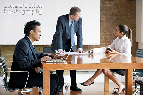 Businessman leaning on a boardroom table talking to woman executive Young executive using laptop com