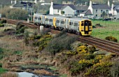 The creation of a Welsh Assembly provided an impetus for the introduction of a Holyhead - Cardiff service operated by Alphaline branded Class 158 units. A pair of these pass Valley in Anglesey on the daily service to Cardiff.
