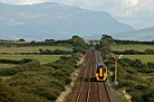 A class 158 DMU heads across Anglesey bound for Holyhead. The mountains of Snowdonia are visible in background. 2003.