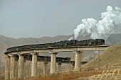 A pair of former China Railways QJ Class 2-10-2s cross the fabled curved viaduct at Simingyi on the Jing Peng pass section of the Ji-Tong Railway in Inner Mongolia.