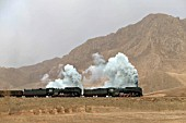 Two ex China Railways QJ Class 2-10-2s climb through the Jing Peng pass on the Ji-Tong Railway in Inner Mongolia.