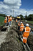 Track workers install cable ducting on West Coast Main Line as a Virgin train approaches from the north. C2003