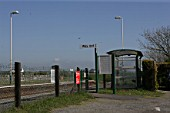 Platform access to Rhosneigr station, Anglesey, North Wales showing lighting, waiting shelter and timetable. 2007