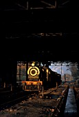 The late afternoon sun shines through the motive power depot at Malakwal in the Pakistans Punjab and illuminates an SPS Class inside cylinder 4-4-0 of British origin. January 1977.