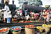 Marketers having taken possession of little used railway track in Accra the Ghanaian capital. The post independence decline of the railway system built under British colonial rule is evidenced. The derelict steam locomotives are British built left an 0-8-