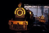 The late afternoon sun shines through the motive power depot at Malakwal in the Pakistan Punjab and illuminates an SPS class inside cylinder 4-4-0 of British origin. In the depot yard can be seen an XA classs Pacific. January 1977.