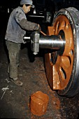 Applying works primer undercoat to newly machined driving wheels at Datong Locomotive Works China.