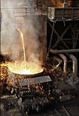 Molten waste from the blast furnaces being poured into ladle wagons prior to being taken to be empted down the slag bank located on the periphery of the complex. A scene at Anshan, Chinas iron & steel capital.