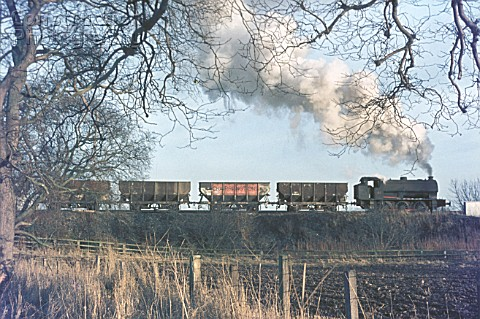 The familiar silhouette of a Hunslet Austerity caught with a rake of loaded wagons at Shilbottle Col