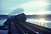 Crossing Arnside viaduct; a late evening view of an ex LMS Black Five at the head of a mixed freight.