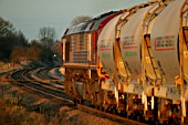 In the golden glow of the early evening sun an EWS Class 66 heads a rake of cement hoppers through Rearsby in the Leicestershire countryside. March 2005