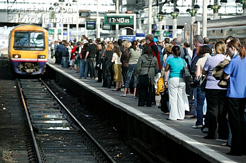 Rush hour travellers throng the platform at Manchester Piccadilly station as a suburban train approa