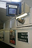 Departure annunciator with signage, advertisements and security mirror at Purley station in Greater London. 2007