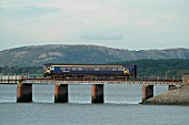 A sunny autumn day in the Lake District sees a single Class 153 DMU cross the Kent estuary at Arnside with a Barrow - Lancaster service. October 2003