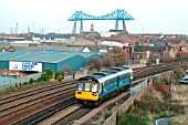 The Arriva Group livery now being applied to rail vehicles is seen on a Class 142 Pacer unit at Middlesbrough as it passes under the shadow of the Transporter Bridge with a Saltburn - Bishop Auckland service. November 2003.
