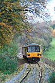 The Esk Valley is a scenic route between Middlesbrough and Whitby which uses one trainset to provide all the daily services. Typical of the route is this Middlesbrough - Whitby service approaching Egton through the autumnal colouring of the valley. November 2003.