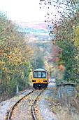 The Esk Valley is a scenic route between Middlesbrough and Whitby which uses one trainset to provide all the daily services. Typical of the route is this Middlesbrough - Whitby services departing from Egton as it threads the autumnal colouring of the Esk Valley. November 2003.