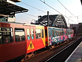 The advertising liveries of Tyne & Wear Metro give some variety as seen at St Peters when the leading set, bearing an advertising livery, compares to the normal red livery seen on the rear set of the departing St James - South Hylton service. November 2003.