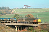 The Angel of the North dominates the ECML and here stands watch over a Class 37 in Load Haul livery with a train of tanks. November 2003.