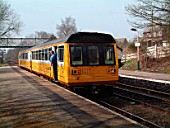 The Merseyrail operation includes branch line services around the area such as the route between Wigan and Kirkby where an end on connection is made with the electric network. The guard of a Rochdale - Kirkby train checks that all is clear before authorising the train to move onto the single track line to Kirkby. April 2003.