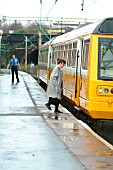 The Merseyrail services operating out of Liverpool Lime St extend beyond the Mersey area including this Liverpool-Manchester Victoria working seen picking up a passenger at Edge Hill. November 2003.