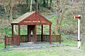 The Talyllyn Railway has an interesting welcome for visitors to its Abergynolwyn station in the shape of a model waiting room complete with signal acting as an entrance to the childrens play area. April 2004.