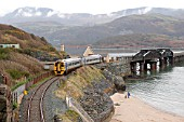 The Mawddach estuary is crossed by the famous Barmouth Bridge, under the shadow of Cadair Idris, to provide a rail link between Machynlleth and Pwhlleli seen being used by a Birmingham - Pwhlleli service as it nears Barnmouth. April 2004.