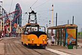 A typical scene on the seafront at Blackpool as one of the towns heritage trams pauses to pick up passengers at the Pleasure Beach.July 2004.