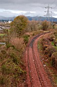 The Stirling to Alloa disused branch line in Scotland. View from road bridge looking over station site to Alloa. April 2005.