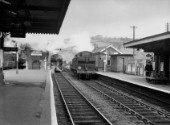 The two centre tracks in this north-looking view of Bargoed station were originally the Rhymney Railways main line from Cardiff to Rhymney. In this view of 18th April 1962, GW 0-6-0PT No.3706 is seen taking water on the left, at the head of a Newport to Brecon through train. GW 0-6-2T No.5601 is seen, right, with a sister engine standing centre. The engines face in the uphill direction, as did all the valleys locomotives, in order to ensure a propoer cover of water over the firebox when climbing the many steep gradients.